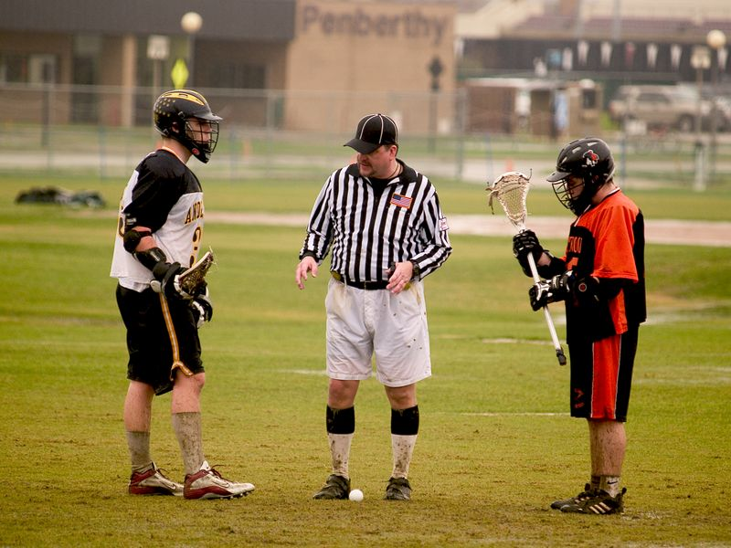 Will Anderson, midfield, and opponent ready for a face-off under the Penberthy Fields sign.