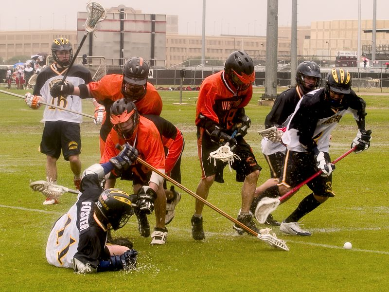 Evan Alexander, Joseph Nguyen and Trevor Brown keep scrambling for the ground ball on the wet field.