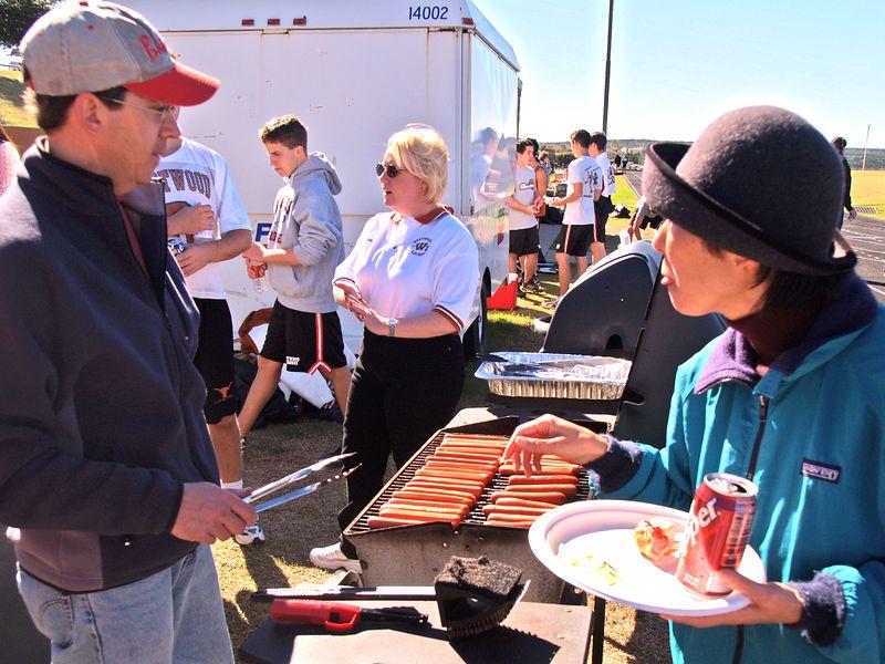 Dan Powers grills hotdogs for the alumni picnic.