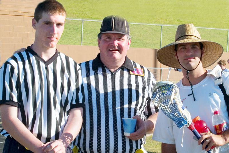 Referees Jeff St. Andre', left and his father Dan St. Andre' pose after the game with beekeeper Noah Fink.