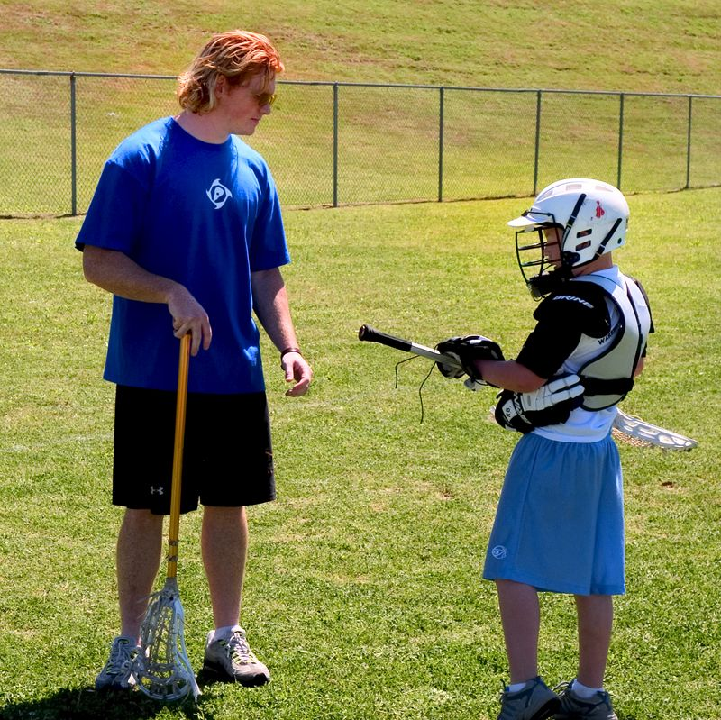 UT lacrosse player works one-on-one with one of the younger clinic participants.