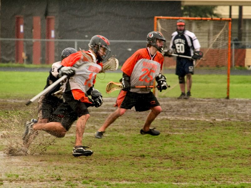Nathan Ostrout sweeps across the field as defender closely trails.
