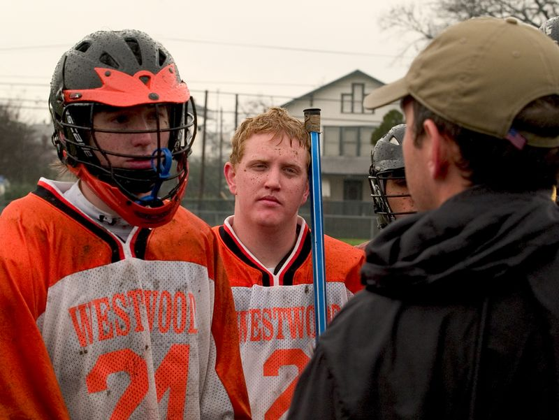 A muddy Ryan Horton and Mike Becherer look and listen to Coach at the half.