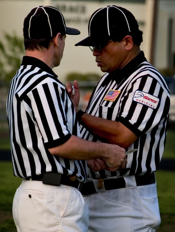 Referees confer after regulation time ended in a draw.