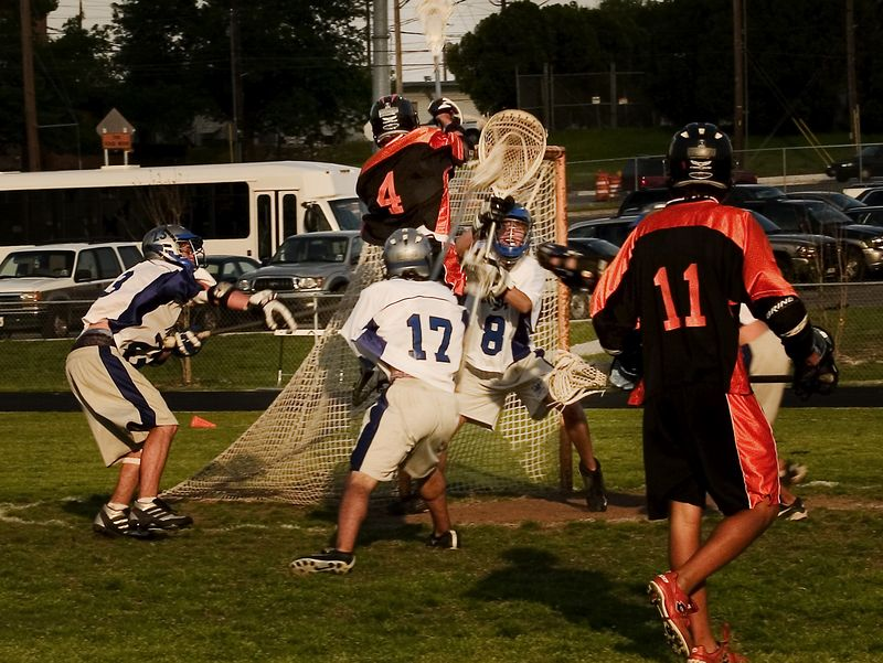 George Lattimore  jumps up at the crease to try to get a shot in past the goalie.