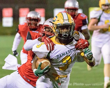 High school senior Markus Vinson of Damascus High School plows forward  with safety Kasim Brown in tow for a first down.