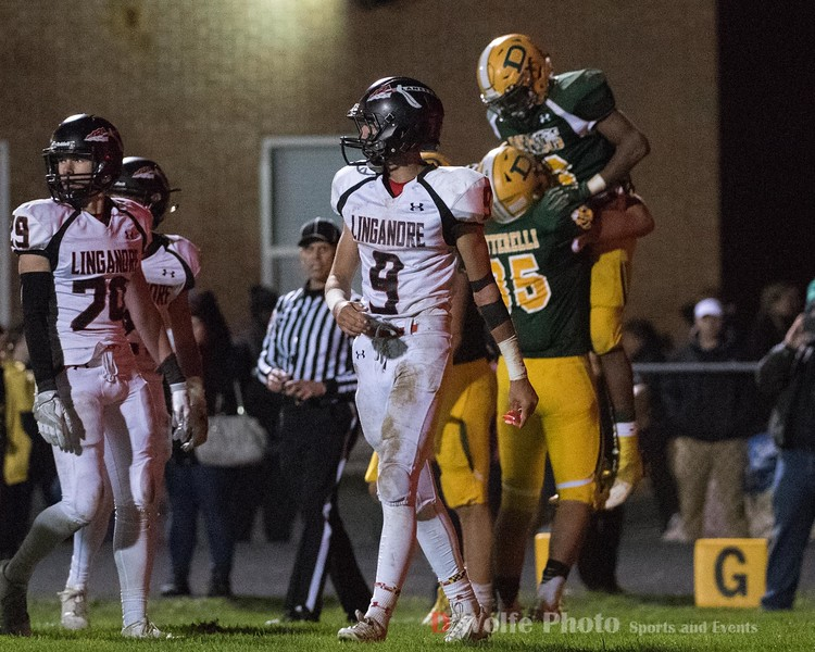 Linganore's safety Tyson Tregoning walks away while Markus Vinson gets hoisted into the air by tight end Matthew Betterelli after scoring his second touchdown of the game.