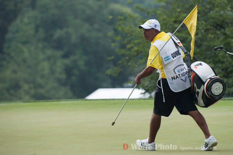 The caddie for Fabian Gomez pulls the flag for the group on the 9th green.