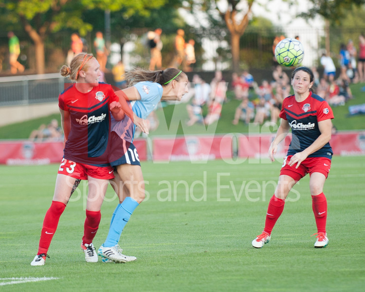 Spirit midfielder Tori Huster and SKy Blue FC's Kristin Grubka mix it up on a header as Diana Matheson watches the track of the ball.