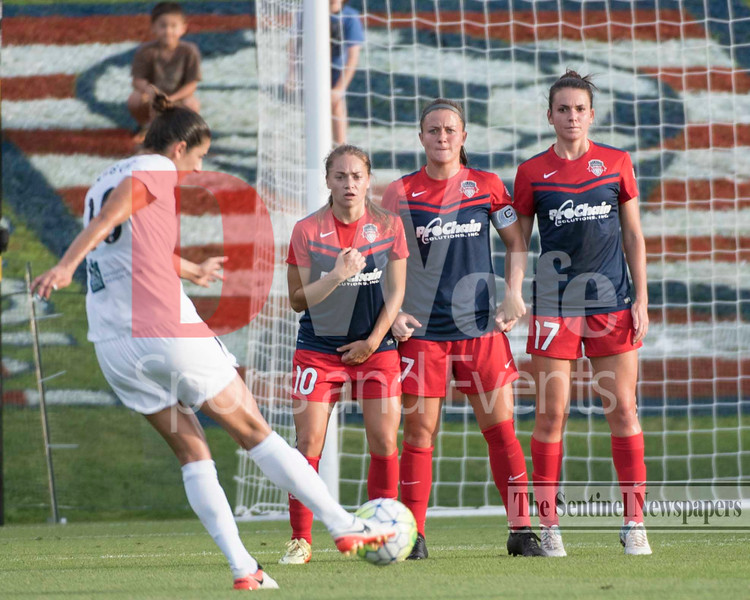 FCKC midfielder Yael Averbuch takes a free kick.  Forming the defensive wall for the Spirit from left to right are Estefania Banini, Chrinstine Nairn, and Cali Farquharson.