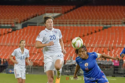 Abby Wambach (20) moving in front of a header by Kencia Marselle (4) directly in front of the goal.