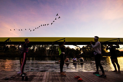The Northeastern University men's rowing team places their boat in the water before practice as the sun rises the day before the Head of the Charles Regatta on Oct. 20, 2017 in Boston, Massachusetts.