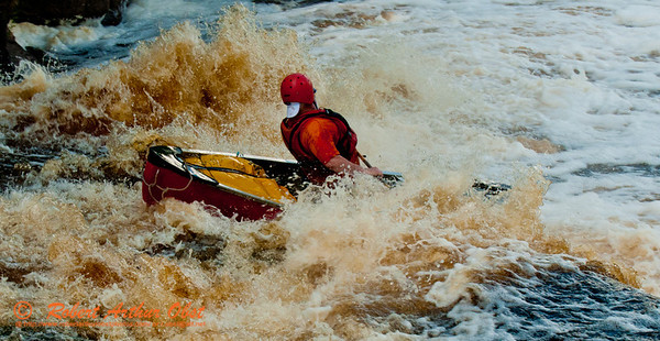 Close-upof an  open canoeist flying through the whitewater turbulence of the final drop of Big Smokey Falls at 744 CFS on the wild Wolf River Section 4 within Menominee Indian Nation  (USA WI Keshena)
