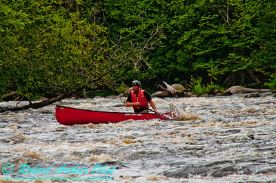 Veteran canoeist and teacher Charlie Frisk with his open canoe at 619 CFS in Crowle Rapids on Section 3 of the wild Wolf River during springtime (USA WI White Lake)