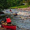Playful kayakers and canoeists in Gilmore's Mistake Rapids at 619 CFS on Section 3 of the wild Wolf River (USA WI White Lake)