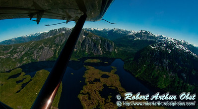 View from a Float Plane of Rugged snow covered mountains and deep blue lakes and green marshlands within Misty Fiords National Monument (USA Alaska Ketchikan)