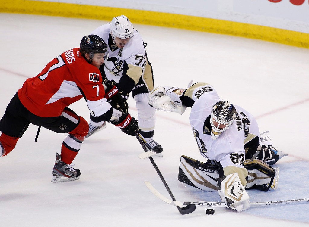 The Ottawa Senators Kyle Turris, left, tries to score on the Pittsburgh Penguins goaltender Tomas Vokoun while the Penguins Evgeni Malkin reaches for the puck during the second period of game four of their Stanley Cup Eastern Conference semi-final NHL hockey game at Scotiabank Place in Ottawa on Sunday, May 19, 2013. THE CANADIAN PRESS/ Patrick Doyle