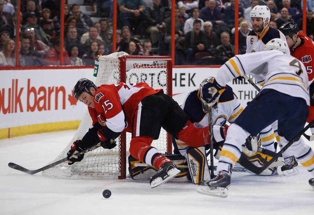 OTTAWA, ONT.: FEBRUARY 6, 2014 -- Ottawa Senators Chris Neil dives for the puck in front of Buffalo Sabres goaltender Jhonas Enroth during the first period of their NHL hockey game in Ottawa, Ont., February 6, 2014.  (Patrick Doyle / Ottawa Citizen)   (For SPRT story by No Reporter)  ASSIGNMENT NUMBER 115972