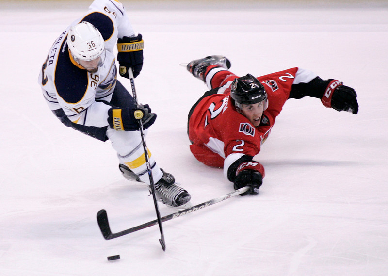 The Ottawa Senators Jared Cowen (R) reaches for the puck as he falls in front of the Buffalo Sabres Patrick Kaleta during the second period of their NHL hockey game at Scotiabank Place in Ottawa, March 10, 2012. Patrick Doyle