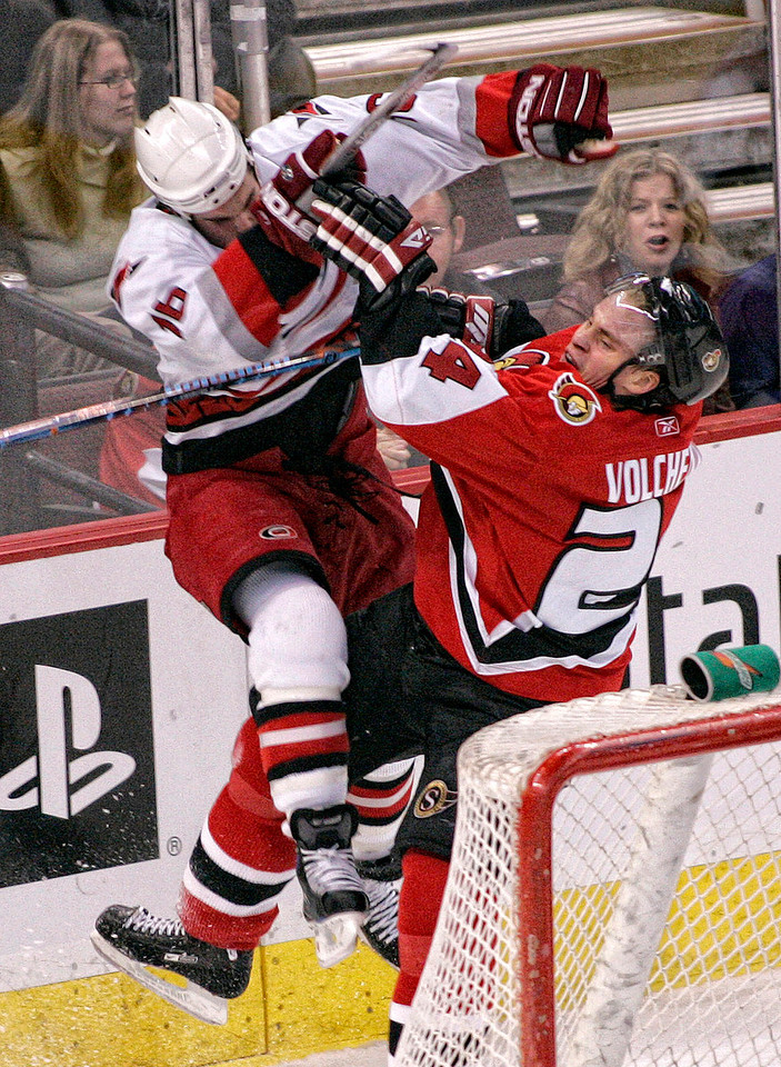 The Carolina Hurricanes' Andrew Ladd (L) collides the Ottawa Senators' Anton Volchenkov (R) during second period action of their NHL hockey game in Ottawa, February 28, 2007. Photo by Patrick Doyle.