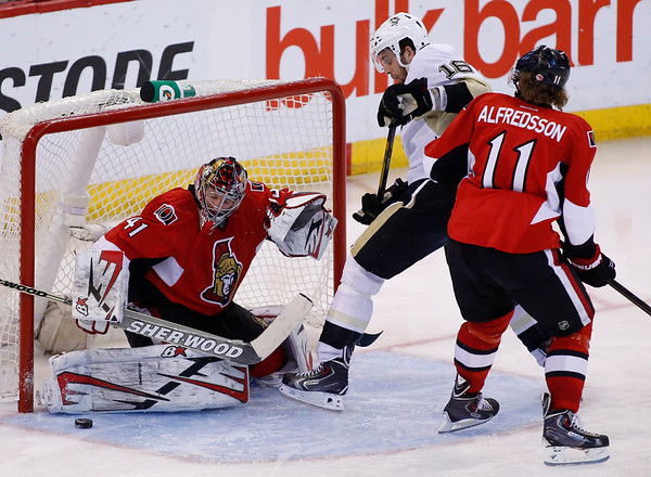 The Ottawa Senators goaltender Craig Anderson, left, makes a save while the Pittsburgh Penguins Brandon Sutter and Senators Daniel Alfredsson jostle in front of the net during the first overtime period of game four of their Stanley Cup Eastern Conference semi-final NHL hockey game at Scotiabank Place in Ottawa on Sunday, May 19, 2013. THE CANADIAN PRESS/ Patrick Doyle