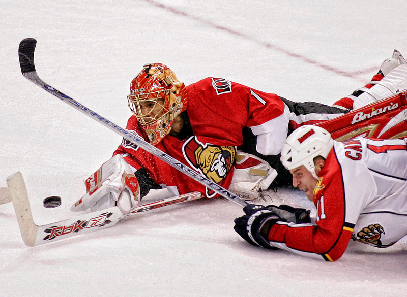 The Ottawa Senators' goaltender Ray Emery (L) and the Florida Panthers' Gregory Campbell (R) dive for the puck during third period NHL hockey action in Ottawa, October 20, 2007. Photo by Patrick Doyle.