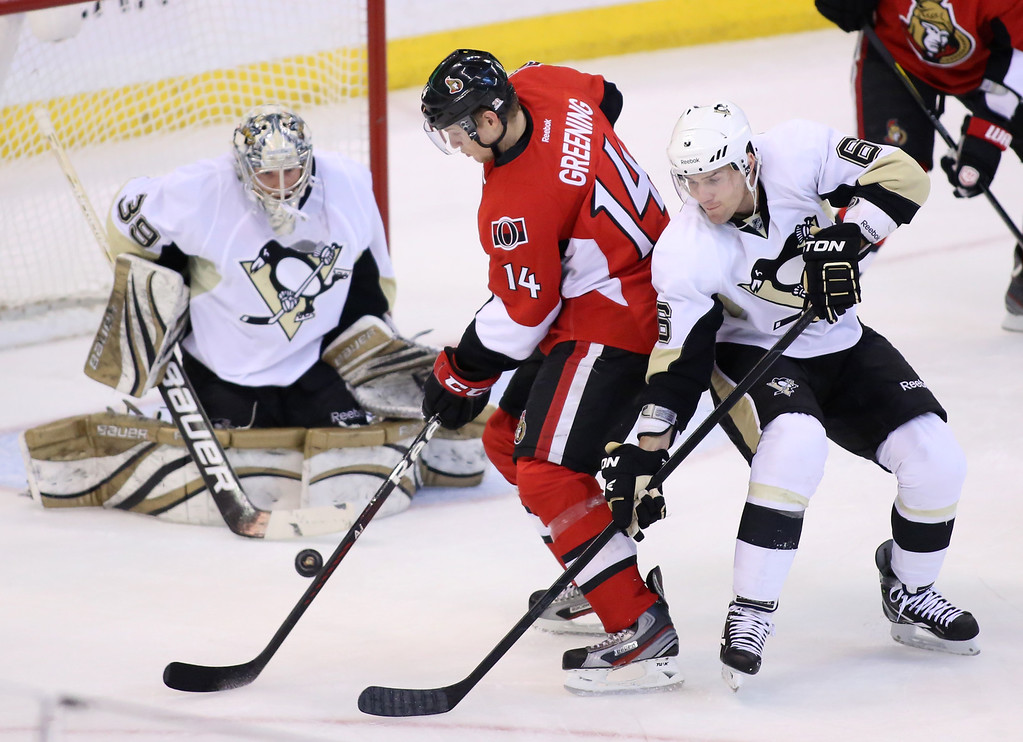 The Ottawa Senators' Colin Greening (C) and The Pittsburgh Penguins' Ben Lovejoy (R) struggle for the puck in front of Penguins' goaltender Brad Thiessen during the first period of their NHL hockey game at Scotiabank Place in Ottawa, March 24, 2012. Photo by Patrick Doyle