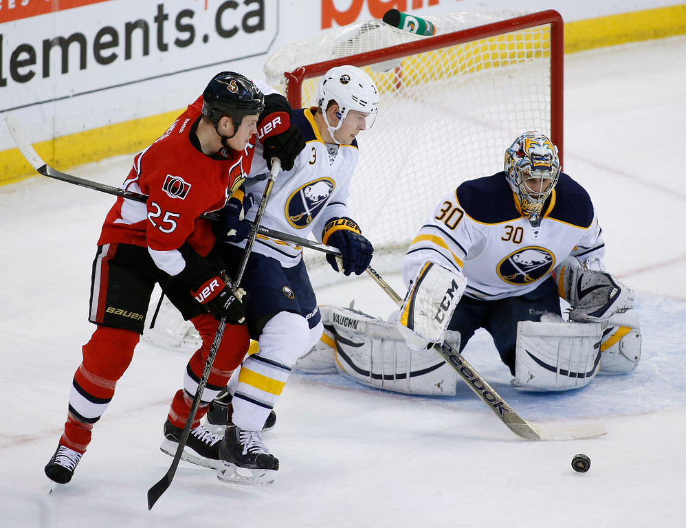 Ottawa Senators Chris Neil, left, and the Buffalo Sabres Mark Pysyk struggle for the puck in front of Sabres goaltender Ryan Miller during the first period of their NHL hockey game at Canadian Tire Centre in Ottawa on Thursday, December 12, 2013. THE CANADIAN PRESS/ Patrick Doyle