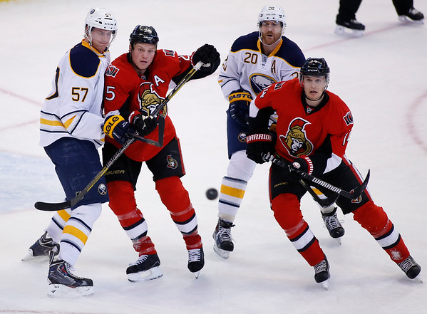 Buffalo Sabres Tyler Myers, left to right, Ottawa Senators Chris Neil, Sabres Henrik Tallinder and Senators Colin Greening chase the puck during the third period of their NHL hockey game at the Canadian Tire Centre in Ottawa on Thursday, December 12, 2013. THE CANADIAN PRESS/ Patrick Doyle