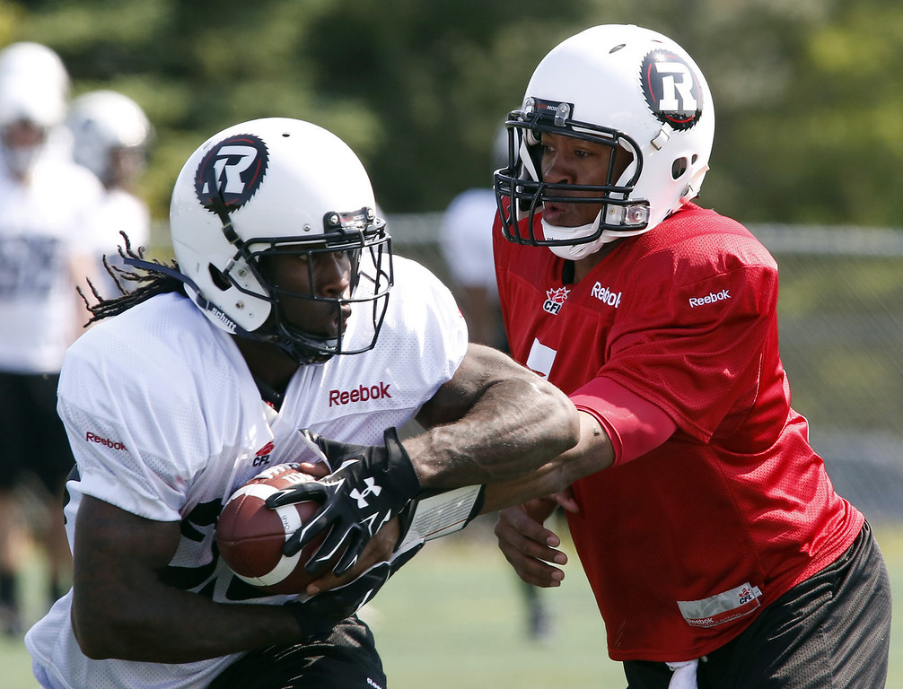 Ottawa Redblacks quarterback Henry Burris (R) hands off the ball to Chevon Walker at the second day of CFL training camp at Keith Harris Stadium in Ottawa on Monday, June 2, 2014.  Photo by Patrick Doyle.