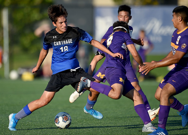 Carthage's Jesus Alvarado (18) tries to get past Monett players Joey Semerad (8) and David Moncivaiz (9) during their scrimmage at the Joplin Jamboree on Tuesday night at Joplin High School.<br /> Globe | Laurie Sisk