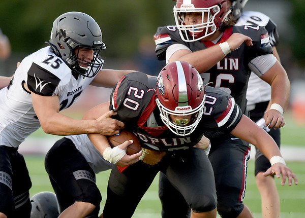 Joplin's Isaiah Davis (20) fights to get past Willard's Jed Brandon (25) as Logan Myers (76) looks on  during the Eagles season opener on Friday night at Junge Stadium.<br /> Globe | Laurie Sisk