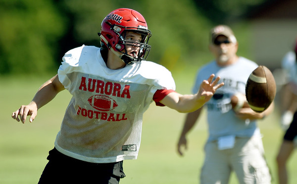 Aurora quarterback Jay Lee runs the option as Coach Craig Weldy looks on during practice on Wednesday at Aurora High School.<br /> Globe | Laurie Sisk