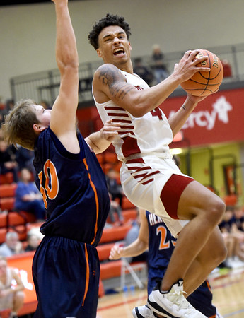 Joplin's Dakarai Allen (4) drives to the basket as Heritage's Kyle Ingram (40) defends during their game in the 4 States Challenge on Saturday night at Webb City.<br /> Globe | Laurie Sisk