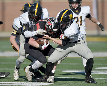 Cassville's DJ White, left and Jacob Olbertz, right, try to bring down Odessa's Luke Malizzi during their Class 3 Championship game on Saturday at Columbia. Globe | Lurie Sisk