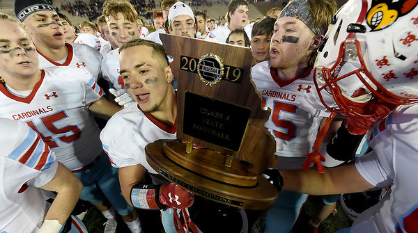 Webb City linebacker Sergio Perez is surrounded by teammates as he holds the Missouri Class 4 Championship trophy on Friday at Columbia after a 48-0 win over Platte County. Globe | Laurie Sisk