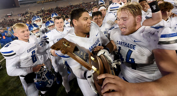 Oscar Campa, center left, hands the Class 5 Championship trophy to fellow Carthage senior Kale Schrader after the Tigers overtime win on Saturday night at Columbia. Schrader was injured on the last play of the game.<br /> Globe | Laurie Sisk
