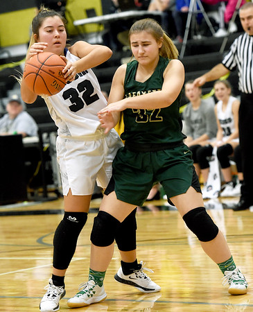 From the left: Neosho's Maile Gindling and St. Joseph Lafayette's Ellie Wattenbarger battle for a loose ball during their first round game in the Neosho Holiday Classic on Thursday at Neosho Junior High School.<br /> Globe | Laurie Sisk
