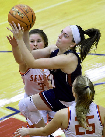 Joplin's Brynn Driver (21) drives to the basket as Seneca's Chelsea Beville (34) and Makayla French (25) defend during their game on Friday night at Seneca.<br /> Globe | Laurie Sisk