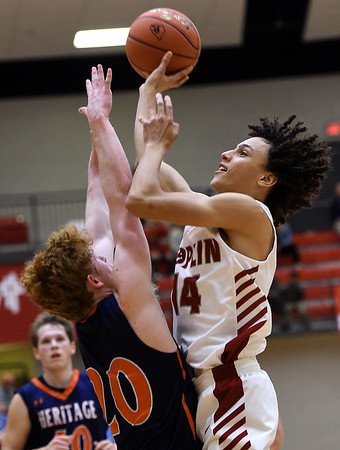 Joplin's Always Wright (14) scores over Heritage's Logan Glenn (20) during their game in the 4 States Challenge on Saturday night at Webb City.<br /> Globe | Laurie Sisk