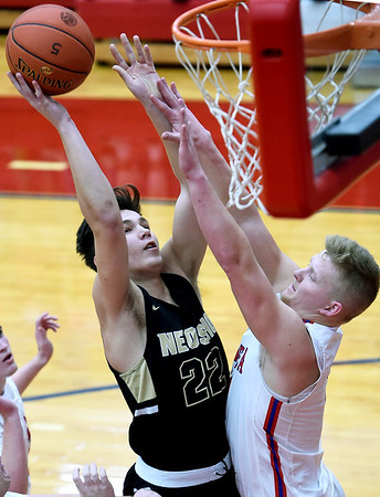 Neosho's Dalton Brodie (22) puts up a shot as Seneca's Levi Ketchum defends during their game on Friday night at Seneca.<br /> Globe | Laurie Sisk