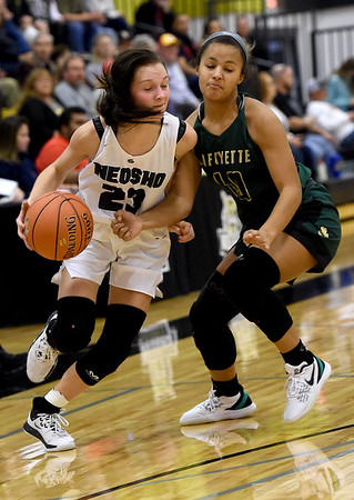 Neosho's Olivia Hixson (23) drives past St. Joseph Lafayette's Jazlyn King (40 ) during their first round game in the Neosho Holiday Classic on Thursday at Neosho Junior High School.<br /> Globe   Laurie Sisk