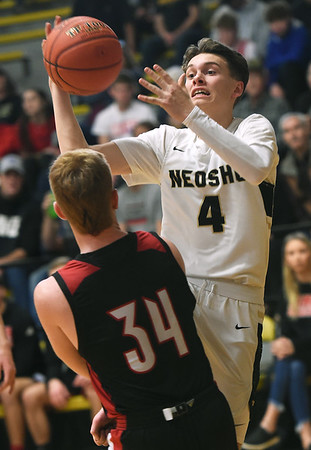 Neosho's Chase Flynn (4) drives to the basket as Lamar's Case Tucker (34) defends during their first round game in the Neosho Holiday Classic on Thursday at Neosho High School.<br /> Globe | Laurie Sisk