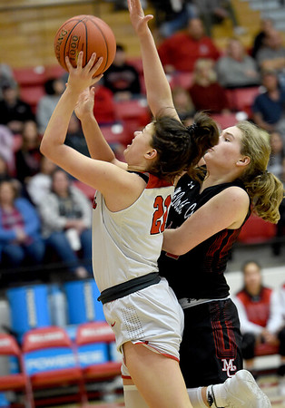 Carl Junction's Jessa Hylton (21) scores in transition as McDonald County's Jaylie Sannie (41) defends during their game on Thursday night at CJHS.<br /> Globe | Laurie SIsk