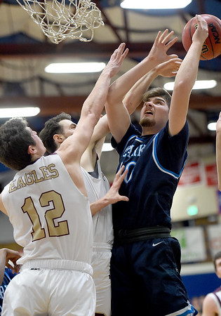 Ozark Christian's Parker Sutton (40) battles Faith Baptist's nathan Kek (12) and Noah Boyer (44) during their first round game of the Midwest Christian College Conference tournament on Thursday night at OCC.<br /> Globe | Laurie Sisk