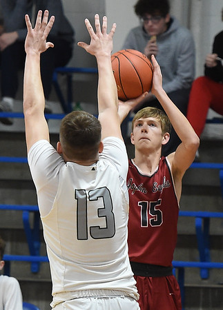 Joplin JV's Micah Bruggeman (15) shoots from the perimeter as College Heights' Jacob Bogar (13) defends during the championship game at the McAuley Warrior Classic on Saturday at McAuley.<br /> Globe | Laurie Sisk