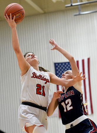 Carl Junction's Jessa Hylton (21) drives to the basket as Joplin's Gabriella Quinn (12) defends during their game on Tuesday night at CJHS.<br /> Globe | Laurie Sisk