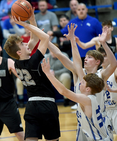 College Heights' Connor Burton (22) scores over McAuley's Daniel Wagner (32) and Thomas Black during their game on Friday night at McAuley.<br /> Globe | Laurie Sis