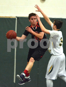 Photo by Albert J. Marro   Twin Valley's Brett Swanson (24) keeps the ball alive as West Rutland's Drake Jankowski (34) defends during Saturday's game in Westside. Twin Valley pulled away in the fourth quarter and won 60-42.