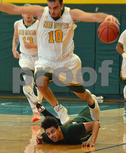 Photo by Albert J. Marro   Green Mounatin's Javier Lugris (10) literally runs over Castleton player after a collision chasing a loose ball during Saturday's game in Poultney. GMC won 80-68